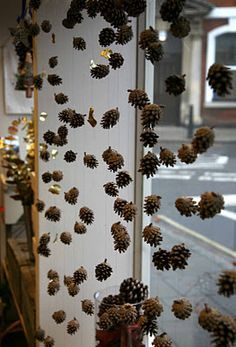 Simple & natural Christmas window display using small pine cones.