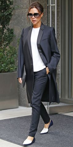 Victoria Beckham gave her street style a dapper spin, stepping out in a pair of tailored pants that she styled with a plain white tee, a sleek tuxedo coat, and two-toned flats.