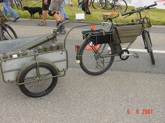 Swiss military bike with trailer. Trailer loaded with artillery shell tubes.