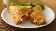 """Crescent Pizza Pockets:   1 can refrigerated crescent dinner rolls 1/4c pizza sauce 3/4c shredded mozzarella cheese 1/2c sliced pepperoni 1t grated Parmesan cheese / Heat oven 375°F. Separate dough into 4 rectangles; press each into 6x4"""".  Press perforations. Spread 1T pizza sauce on half of each rectangle. Sprinkle each w/ 3T cheese top w/ pepperoni. Fold dough diagonally over filling press edges. Sprinkle each triangle w/1/4t cheese. Prick each to allow steam to escape Bake until golden br..."""