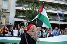 Demonstrators shout slogans and wave flags of Palestine standing in front of the offices of EU in Athens Left wing party supporters together with...