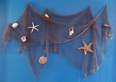 Fisherman Net Decoration | Fish net hung on blue wall decorated with seashells and starfish.