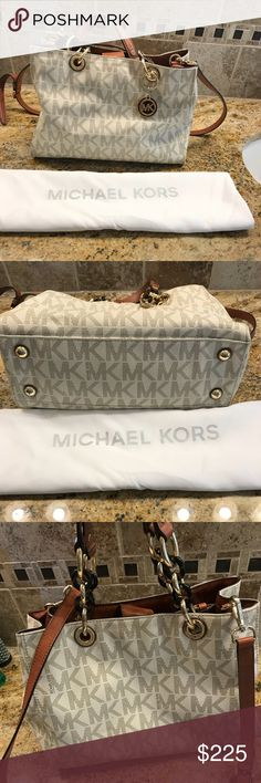 """Gorgeous Michael Kors Satchel 💎 This purse would make a great gift to someone special or even yourself! This white and brown leather bag has gold and amber detail, with a shoulder strap and two arm straps. It has a snap closure with a middle zip compartment (which has a small lipstick stain as pictured), and other zip and non zip pockets. It is in excellent used condition with no wear on the outside. This beautiful bag is 9"""" in height, 11&1/2"""" in width and 5&1/2"""" in depth. Comes with…"""