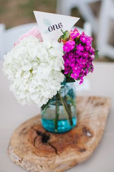 rustic wood as centerpiece with floral arrangement and table number flag #weddingreception #centerpiece #weddingchicks http://www.weddingchicks.com/2014/01/24/true-love-texas-wedding