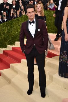 Orlando Bloom wore a Prada bordeaux kid mohair smoking jacket with a black faille shawl lapel and black tuxedo pants at the Met Museum opening of Manus x Machina in New York.