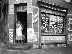 """Depression """"bread wars"""", corner store on Bourke & Fitzroy Streets, Surry Hills, Sydney, 21 August 1934 / Sam Hood Description: Note: The shop still stands, worn step included, but the area has gentrified since its slum days"""