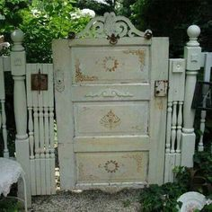 Old vintage door, stair well railing items, etc turned into a garden gate.