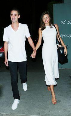 Miranda Kerr wears a white midi dress with nude heels and a black bucket bag