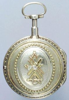 """A late 18th Century French verge in a silver and gold consular case with Masonic decoration. Silver regulator dial with blue steel indicator. Round pillars. Wound through the white enamel dial with Roman and Arabic numerals, fine pierced gilt hands. Unusual silver consular case decorated with applied gold """"pique"""" pins to the bezels. The back set with applied gold and silver Masonic symbols within an oval. Signed: Amel at Fils - Mopteau. C. 1780."""