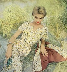 Jean Patchett in a flower-print dress with a star neckline and a sleeveless brown linen jacket lined in the same flower print by Eisenberg, jewelry by Napier. Photo by Clifford Coffin. Vogue, December 1953.