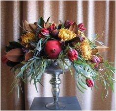 Fall flower arrangement in mercury glass vase using pomegranates, cranberries & figs. By Vibrant Flowers in Portland, Oregon @Vibrant Flowers