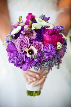 Stand out with a bright wedding bouquet that will contrast with the shoreline's natural and neutral shades. This beach wedding bouquet consists of lilac roses, violet orchids, Picasso calla lilies, and bright pink peonies.