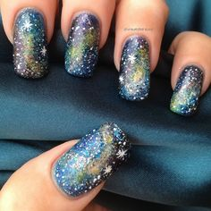 Create a gorgeous galaxy on your nails by sponging on nail polishes and glitters!