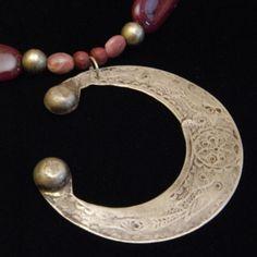 Collier dans les tons fuchsia foncé. Il est fait de perle en bois, en pâte de verre, en résine polymère et en métal blanc ainsi que deux petites pierres rose de Rhodonite. Le pendentif en Argent est à l'origine une ancienne broche Berbère.