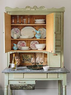 Most of the Hoosier cabinet's contents—like the whiteware platters and crystal candlesticks—came with the house. #countryliving #kitchens
