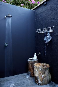 this is a gorgeous outdoor shower, love the dark paint, which creates an oasis of calm and ties together the different wall textures. also love the organic feel that the stump seating provides, along with the tile. a luxe outdoor shower!
