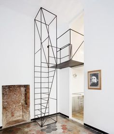 A wireframe staircase leads to a new top floor inside this renovated apartment in Milan by architect Francesco Librizzi.