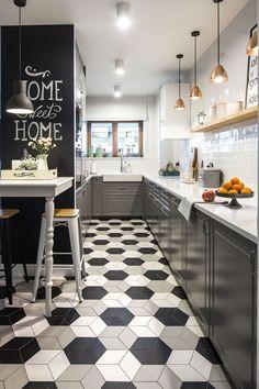 W aranżacji tej łazienki połączono najmodniejsze trendy wnętrzarskie ostatnich sezonów: szare szafki kuchenne w angielskim stylu, różowe złoto wiszących lamp, czarną farbę tablicową, emaliowane, pastelowe kanki, połyskujące, białe płytki, brak górnych szafek w kuchni i geometryczne płytki z optyczną iluzją.