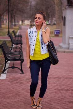 Jeans, camiseta amarilla, sandalias marrones y cazadora vaquera sin mangas con algo de pedreria