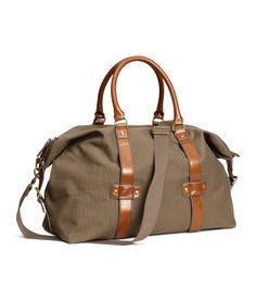 Dark beige cotton canvas weekend bag with faux leather handles, side fasteners for expansion, and detachable, adjustable shoulder strap. Leather Handle, Leather Bag, Canvas Weekender Bag, Sac Week End, M48, Men's Totes, Brown Purses, Mk Bags, Luggage Bags