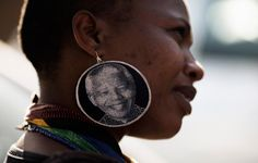 A South African woman wearing large earrings bearing a picture of former South African president Nelson Mandela stands outside the Medi Clinic Heart Hospital in Pretoria, where Mandela lay in critical condition. (Photo: AFP - Filippo Monteforte