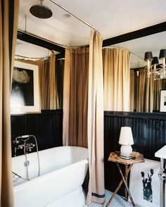 Mark D. Sikes & Michael Griffin Photo - Camel-colored shower curtains and a freestanding tub in a black bathroom