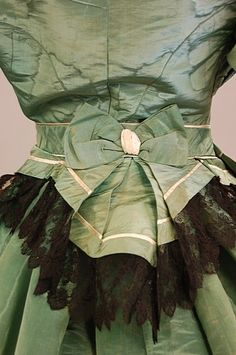Circa 1865 formal gown, A green watered silk with lightly padded bodice trimmed with cream and black lace and bows, the horizontally banded skirt with matching waist-sash.