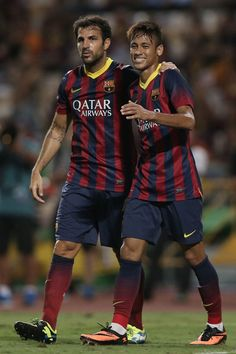 Neymar JR #11 (R) of Barcelona celebrates scoring a goal with team mate Cese Fabregas #4  against the Thailand XI during the international friendly match between Thailand XI and FC Barcelona at Rajamangala Stadium on August 7, 2013 in Bangkok, Thailand.