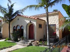 Spanish Bungalow with triple arched windows and tiled arch entry door...stone plaster effect