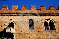 Photo taken with an old building that is located near the back of the Basilica of San Petronio in Bologna in Emilia Romagna (Italy). In the image, which takes up a portion of the facade of the building, you see a small ornamental balcony window and a mullioned window. The battlements of the wall are clearly highlighted by the deep blue of the sky.