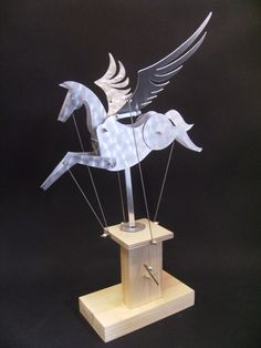 This Pegasus automata has been hand cut from aluminium and the metal has been given a buffed circular pattern . The base is made from wood and