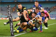 Josh Mansour of the Panthers is bundled into touch by the Bulldogs defense during a rugby match between the Canterbury Bulldogs and the Penrith Panthers at ANZ Stadium in Sydney, Australia.