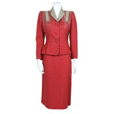 Light brick red wool suit   United States, 1940's   Suit features a single breasted jacket with contrasting putty gray collar and accent panels and studded skirt. Jacket is decorated all over with hand set flat, round silver studs that radiate from the accent panels at shoulders. Jacket is fastened with self fabric covered buttons