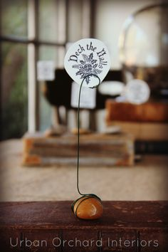 Idea for displaying small pottery pieces with wire and rock . . . and displaying photos, dinner place cards, and such . . .