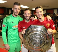 David de Gea Juan Mata and Ander Herrera of Manchester United pose with the Community Shield trophy in the dressing room after the FA Community...