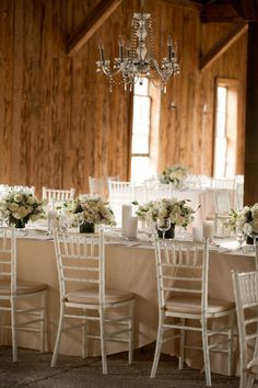 a barn made glamorous with all white details and sparkling chandeliers Photography by Gayle Brooker Photography / gaylebrooker.com, Event Planning   Design by Kristin Newman Designs / kristinnewmandesigns.com/, Floral   Lighting Design by Gathering Floral   Event Design / gatheringevents.com