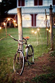 rusty bike + fence + string lights