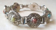 A Vintage Celtic style faux gemstone panel bracelet The bracelet is formed from silver tone metal with seven panels Each panel has a centrally set