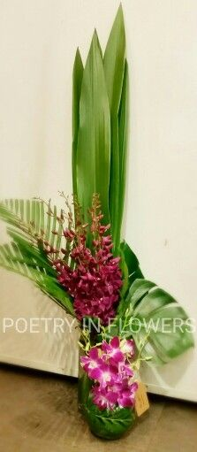 Tall corporate flowers vase. Singapore orchids, gymea leaves.