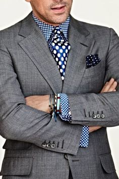 Shop this look on Lookastic:  http://lookastic.com/men/looks/blue-dress-shirt-blue-tie-navy-and-white-pocket-square-grey-blazer/9655  — Blue Polka Dot Dress Shirt  — Blue Polka Dot Silk Tie  — Navy and White Polka Dot Pocket Square  — Grey Blazer