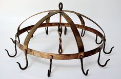 Vintage Pot rack with elegant vintage details including: Blacksmith style twisted brass hooks and bands, copper rivets and turned steel loops. If you love to cook and dont want the newby look of fresh metal, this vintage hanging pot rack might be for you. Its just the right size for a dozen of your favorite kitchen pots, bowls and/or utensils.    Size: 18 across by 12.75 tall (from bottom of hooks to top of steel hanging loop). 12 hanging hooks and one central steel hanging loop.    Weight…