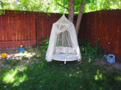 Outdoor swing- made from a mini trampoline.  Easy, sturdy, fun.  The back pillow I made from a crib bumper pad, so it stands up.  The $3.00 net came from a yard sale.  5 long loops of rope hook around the shortened legs (pipe cutter) and up to a strong metal ring.