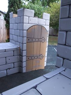 I like the look of the castle door. paint a refrigerator box and use as entrance to preschool classroom. instead of this door leave archway and cover existing door with brown paper and sketch hinges.