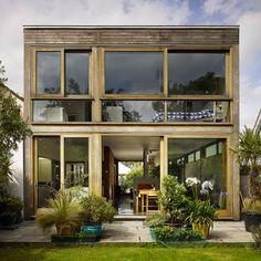 Sliding doors connect John McLaughlin's timber-framed Open House with its garden