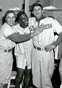 Brooklyn Dodgers Pee Wee Reese, Jackie Robinson and Preacher Roe celebrate winning the 1955 World Series