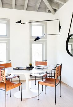Leather chairs around small dining space in eating area with exposed ceiling beams and modern light