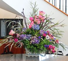 Arrangement from February 11, 2014: protea, hydrangea, roses, fiddle leaf ferns, Ming fern, grevillea, wax flowers, and lisianthus.