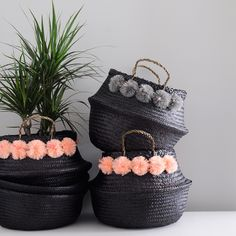 Handmade basket designed by Eliza Gran. A beautiful combination of function and beauty. Hide away clutter or use as a planter. - Handwoven - Color: Black basket with Shell Pink pom poms with bright pi