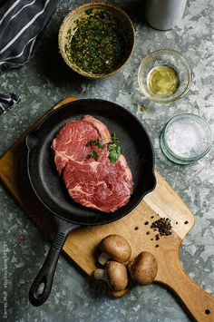Ribeye steak in raw state surrounded by ingredients for preparing the meat.