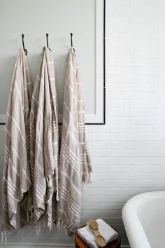 Hooks instead of a towel bar.....I like this....also like the frame around the hooks, sets it off and makes it stylish